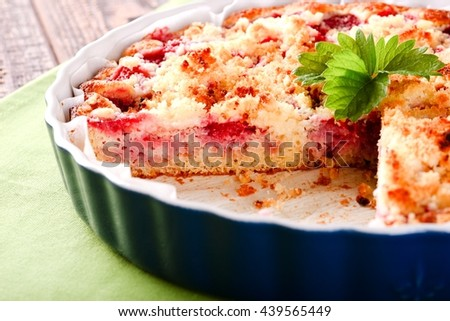 Horizontal photo of strawberry cake with one portion cut off. Green strawberry leaf placed on fruit pie. Pie in blue ovenproof dish on green towel and old brown wooden board. - stock photo