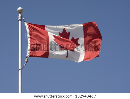 Horizontal photo of the Canadian flag flying with a blue sky.