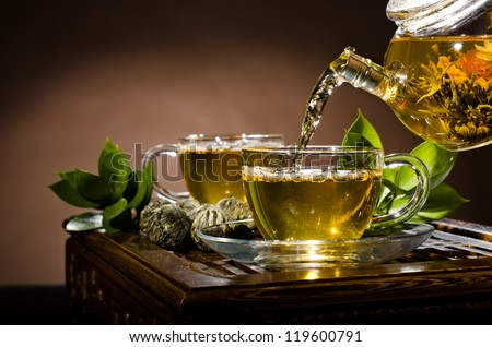 horizontal photo, of the glass teapot flow green tea in cup on brown background,  tea ceremony - stock photo