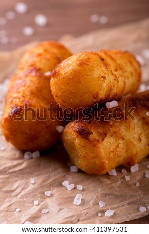 Horizontal photo of three crispy fried potato croquettes. Croquettes are placed on piece of brown crumpled paper on wooden board. Coarse grained salt is spilled around. - stock photo