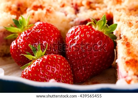 Horizontal photo of three red juicy strawberries on position of cut off portion from sweet fruit strawberry pie in blue ovenproof dish. Fruit with pie in bowl. Detail of three berries with stalks. - stock photo