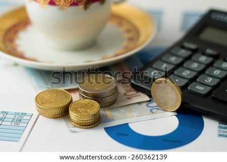 Horizontal photo of Three stacks of coins on other bills placed on paper sheets with pie chart with black calculator and tea cup.