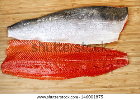 Horizontal photo of two Red Salmon fillets, one skin side up, on natural bamboo cutting board - stock photo