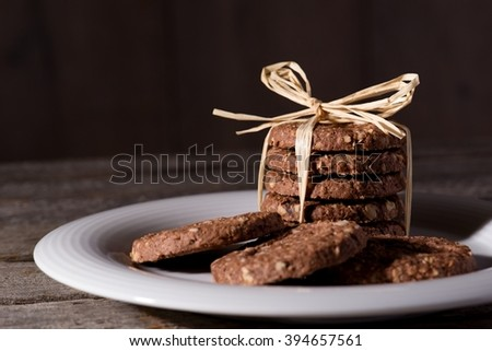Horizontal photo of white plate placed on wooden board with few brown cereal biscuits. Few biscuits are placed in a stack bonded by yellow straw.  - stock photo