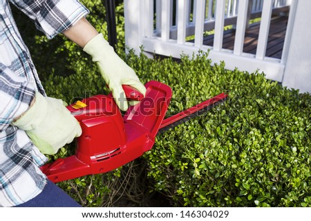 Horizontal photo of woman and power trimmer cutting the hedges with patio in background  - stock photo