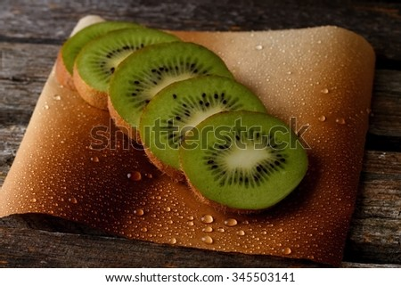 Horizontal photo with few kiwi slices in a row placed on sheet of paper with many water drops on. All is placed on old wooden board.  - stock photo