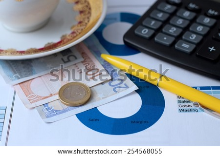 Horizontal photo with paper sheet with printed pie chart, euro bills under coffee cup, yellow pen, black calculator and one euro coin. Photo is with blue tone. - stock photo
