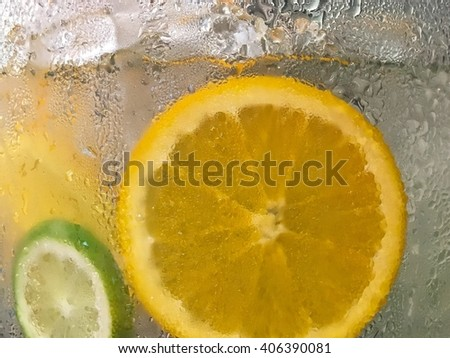 Horizontal picture of lemon and lime in the glass of iced water. Only the water drops on the glass are in focus while the content inside is blurred to make the overall picture look cold and refreshing - stock photo