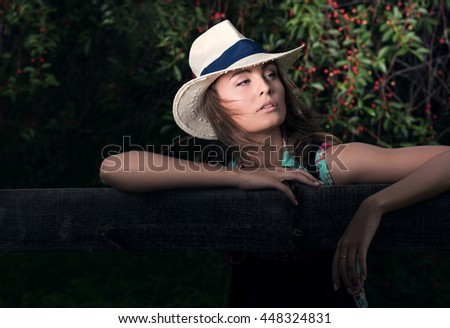 Horizontal portrait in dark tones outdoors. Young attractive woman in the background cherry wood - stock photo