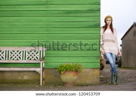Horizontal portrait of a beautiful young Caucasian woman standing outside against a green wooden wall. Possibility for copy space - stock photo