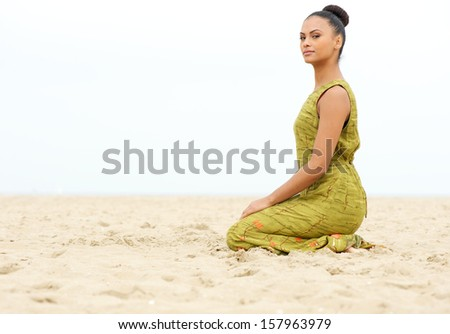 Horizontal portrait of a beautiful young woman sitting alone on sand at the beach - stock photo