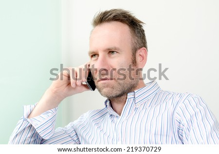 Horizontal portrait of a Caucasian middle-aged handsome man wearing a long-sleeved colorful shirt while having a pleasant conversation on the mobile phone, indoors - stock photo