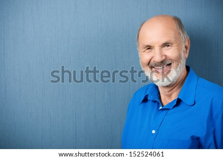 Horizontal portrait of a Caucasian senior male teacher smiling at camera with a blank chalkboard in the background - stock photo