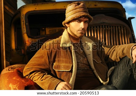 Horizontal portrait of a good looking young male model in brown against a rusty old truck - stock photo