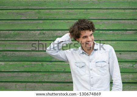 Horizontal portrait of a handsome young man smiling outdoors - stock photo