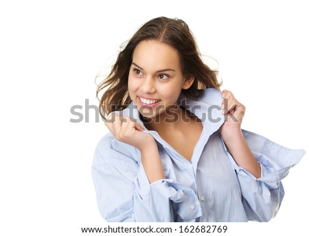 Horizontal portrait of a happy smiling young woman holding shirt and looking away isolated on white