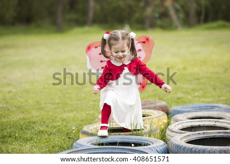 horizontal portrait of a little girl walking on painted tires in a park, looking happy, wearing a white dress, red blouse, red stockings and white slippers, with butterfly wings on her back - stock photo