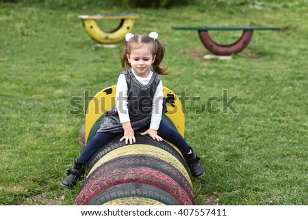 horizontal portrait of a little girl wearing a gray dress and white blouse and  sitting on top of painted tires in a children's playground in spring - stock photo