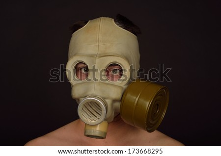 Horizontal Portrait of a Man with a Gas Mask on Black Background - stock photo
