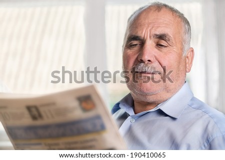 Horizontal portrait of a senior Caucasian man with mustache wearing a grey shirt while reading a daily newspaper at home - stock photo