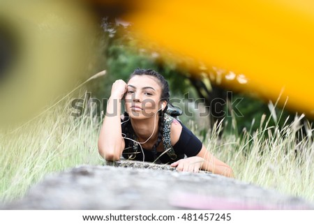 horizontal portrait of a young attractive brunette girl with braided pigtails lying on a stone in a field or park with grown grass and trees around her and blurry foreground