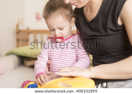 horizontal portrait of a young mother holding her little daughter in pijamas and pacifier in her arms and playing together on the bed in a nursery room - stock photo