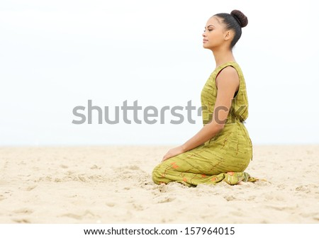 Horizontal portrait of a young woman sitting alone and meditating at the beach - stock photo