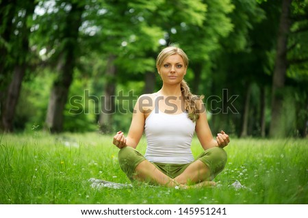 Horizontal portrait of a young woman sitting in yoga position in the park