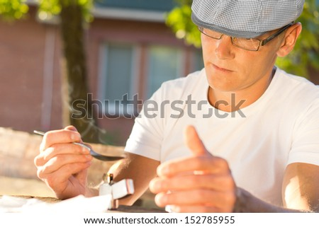 Horizontal portrait of an addicted middle-aged Caucasian man heating soluble heroin in a teaspoon with a lighter, outdoors - stock photo