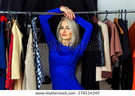 Horizontal portrait of beautiful young blond woman in a clothing store. Happy young lady with a lot of clothes. Shopping concept. - stock photo