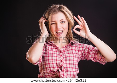 Horizontal portrait of beautiful young woman in checkered shirt and headphones. Ok gesture - stock photo