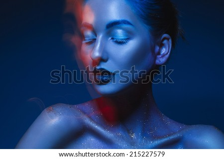 Horizontal portrait of sensual woman in blue body art in studio - stock photo