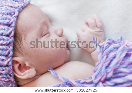 Horizontal portrait of the sleeping baby in purple hat - stock photo