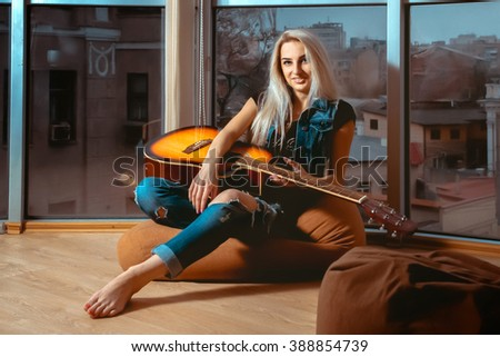Horizontal portrait of young beautiful girl with guitar in hands. Girl with guitar. Woman playing guitar. leisure with guitar. - stock photo