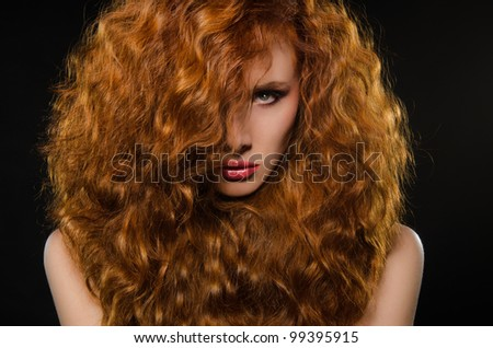 horizontal portrait of young woman with red hair on black background - stock photo
