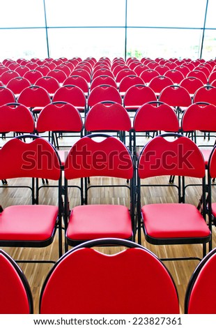 Horizontal rows of red chairs in a public hall - stock photo