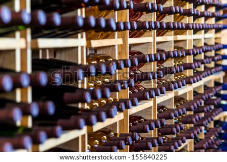 Horizontal rows of wine bottles in a cellar - stock photo