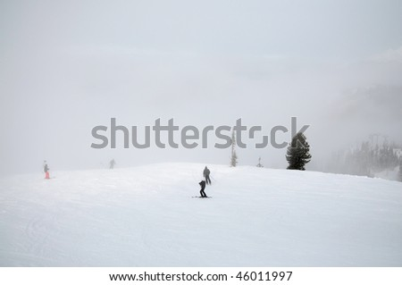 Horizontal scenic image of skiers on a cloudy hill