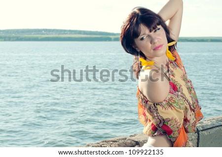 Horizontal shot of a beautiful young woman relaxing outdoors - stock photo