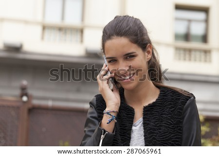 Horizontal shot of a beautiful young woman smiling and talking on the mobile phone.  The picture was taking outdoors with a building in the background in a city. - stock photo