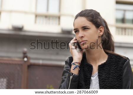 Horizontal shot of a beautiful young woman talking on the mobile phone.  The picture was taking outdoors with a building in the background in a city. - stock photo