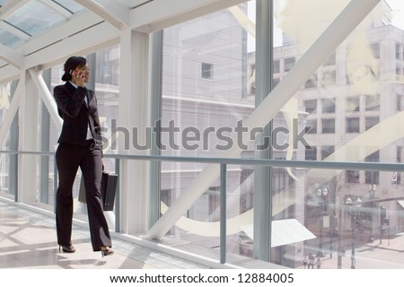 Horizontal shot of a businesswoman, talking on a cellphone, walking through a skybridge - stock photo
