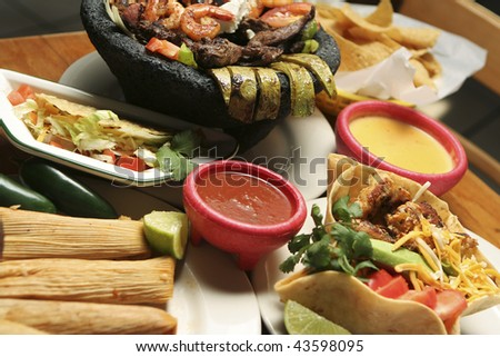 Horizontal shot of a variety of Mexican dishes. Shallow dof with central portion of image in focus. - stock photo