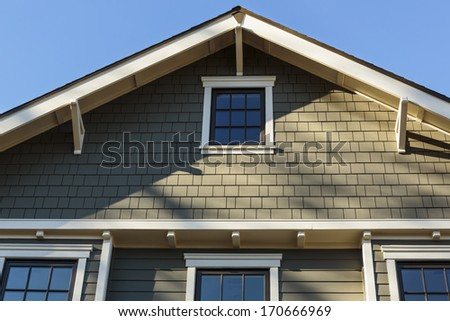 Horizontal shot of an upscale home with blue sky and sun shadows/ Front Roof line of an Upscale Home