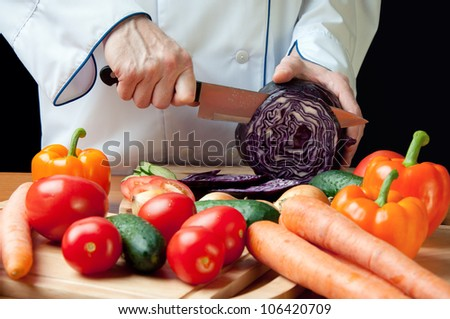 Horizontal shot of chef's hands cutting red cabbage head - stock photo