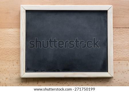 Horizontal shot of empty blackboard lying on wooden desk - stock photo