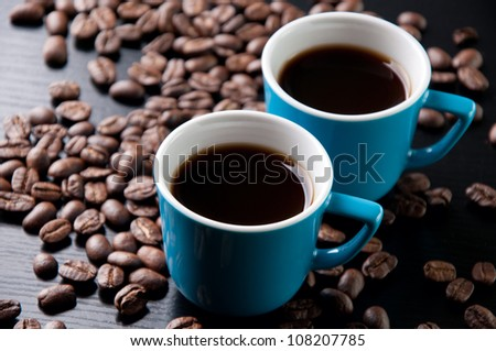 Horizontal shot of espresso and roasted coffee beans, close-up - stock photo