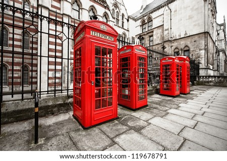 horizontal shot of four red phone boxes on London's street - stock photo