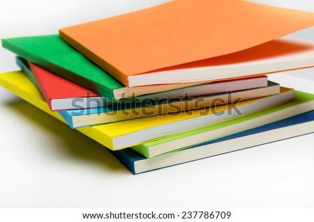 Horizontal shot of isolated on the white background pile of colorful notebooks - stock photo