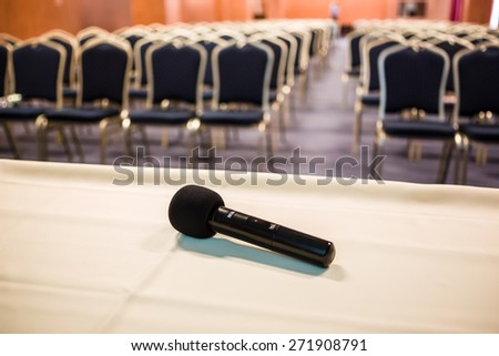 Horizontal shot of microphone and chairs in auditorium - stock photo
